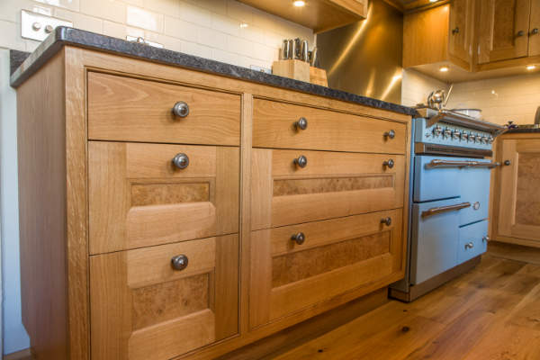 Cabinets with Drawers that have pewter handles and burr oak veneers on the panels. The cabinets have granite worktops