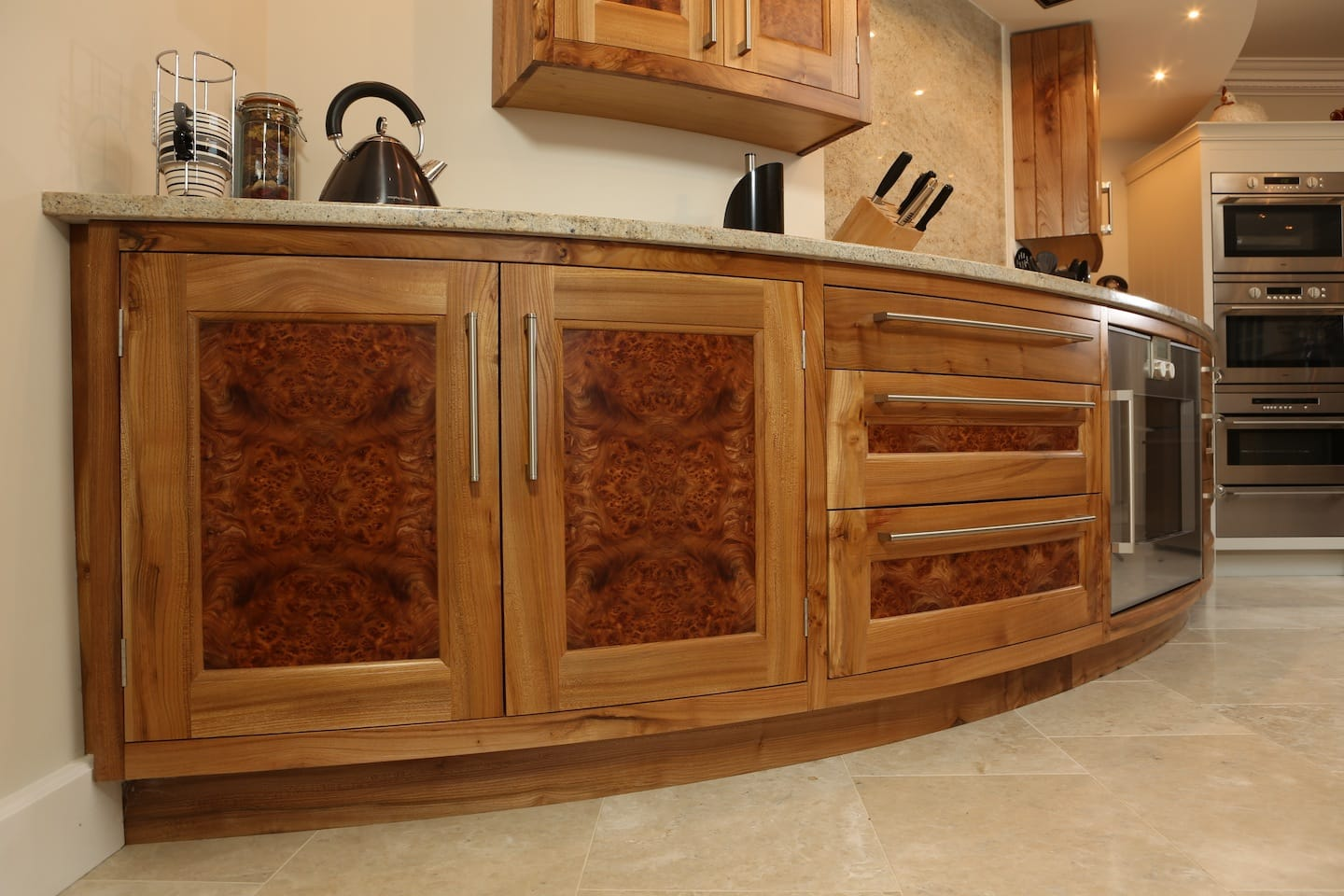 detail view of curved solid oak kitchen cabinets with integrated oven and gas hob, marble worktops