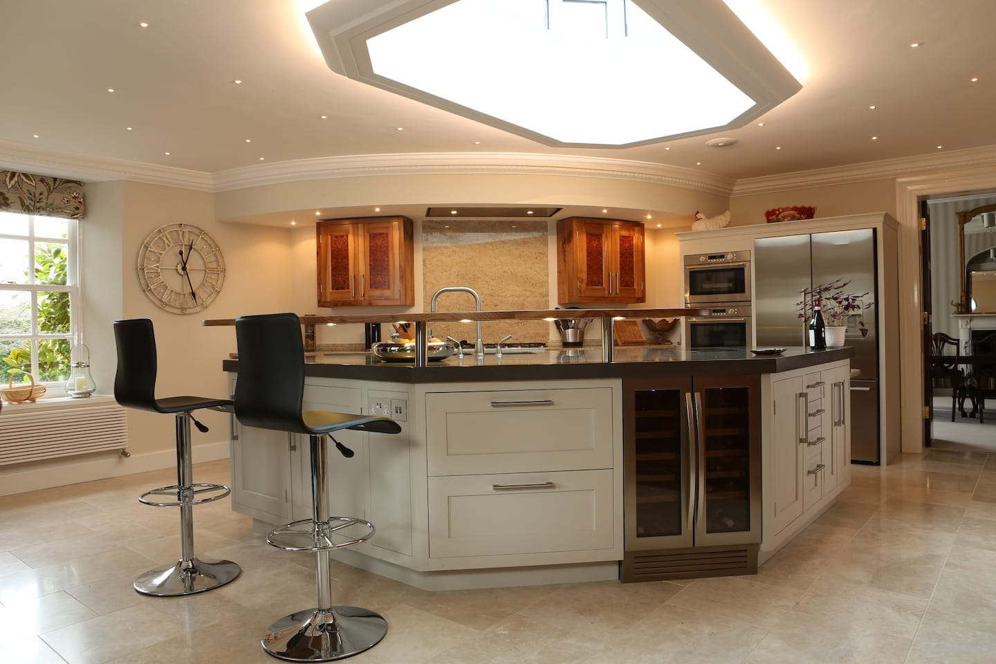 View of kitchen island with solid elm breakfast bar, high stools, integrated wine fridge, induction hob and storage