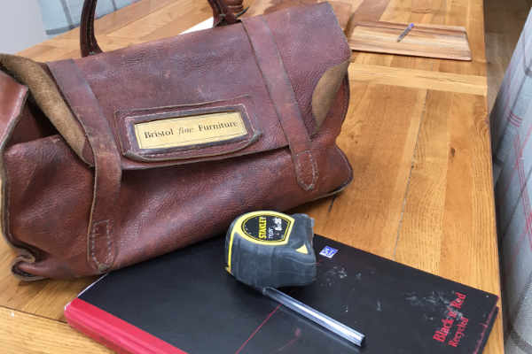 Notebook tape measure and toolbag on kitchen table