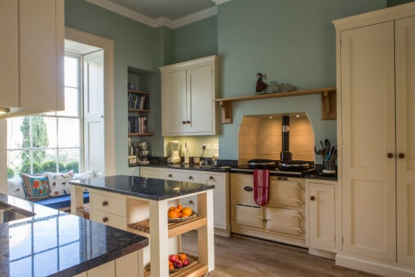 Wide view of a kitchen showing Aga range cooker, window seat and mobile kitchen island with granite worktop